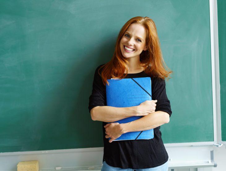 Woman holding folder in front of chalkboard